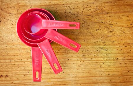 Red measuring cups in different sizes on a timber board Stock Photo - 8437664