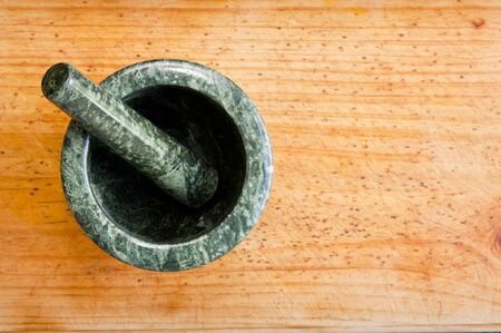 An empty mortar and pestle from above on a timber background photo