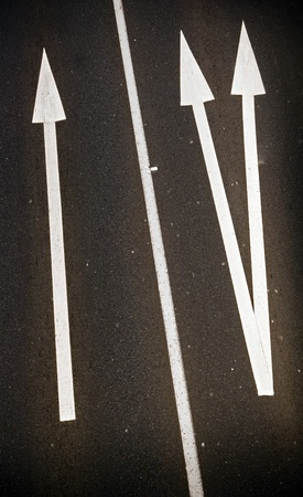 Large painted arrows on a freeway contrast with the bitumen photo