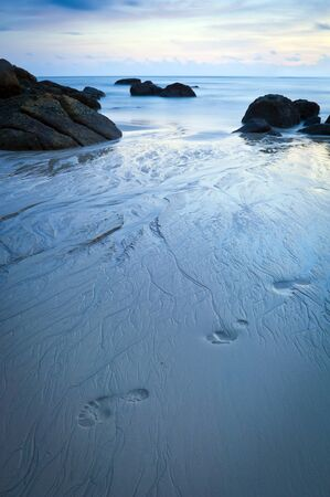 timelapse: Time-lapse of beach at dusk with footprints in sand Stock Photo