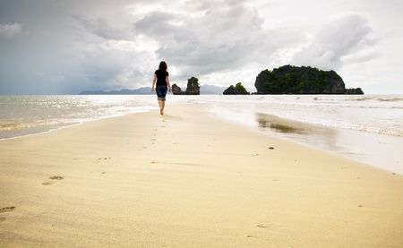 langkawi island: A young woman walks alone on a beach