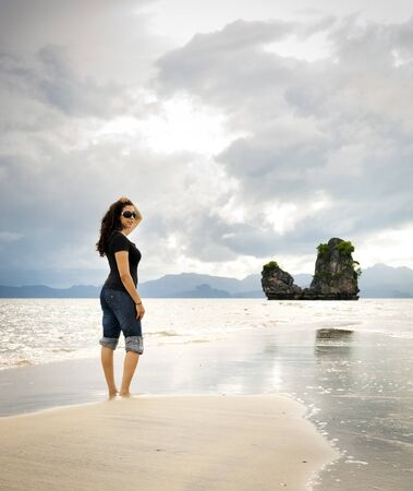 A young woman walks alone on a beach photo