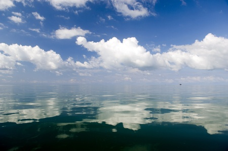 gleam: Large white clouds gleam over deep waters