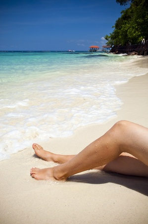 Womans legs on beautiful tropical beach with bright sand photo
