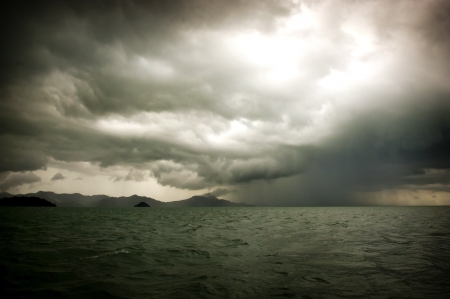 storm clouds: Huge storm clouds with rain over a rough ocean Stock Photo