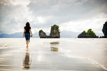 A young woman walks alone on a beach Stock Photo - 10203181