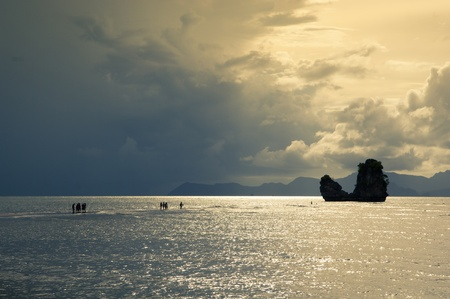 langkawi island: Silhouetted people seemingly walking on water leading to an island