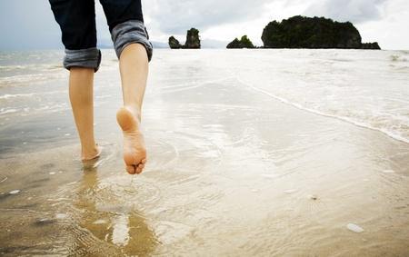 caminando: Una joven mujer camina solo en una playa