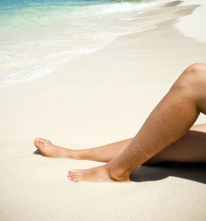 langkawi island: Womans legs on beautiful tropical beach with bright sand