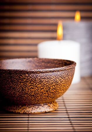 An exotic Asian style wooden bowl on bamboo with candles Stock Photo - 10688433