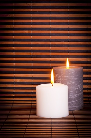 Two burning candles on a bamboo background with copy space photo