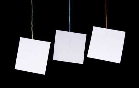 Multiple white paper tags hang on colorful string over black Stock Photo - 10688421