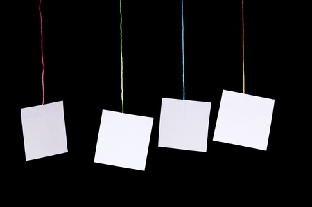 Multiple white paper tags hang on colorful string over black