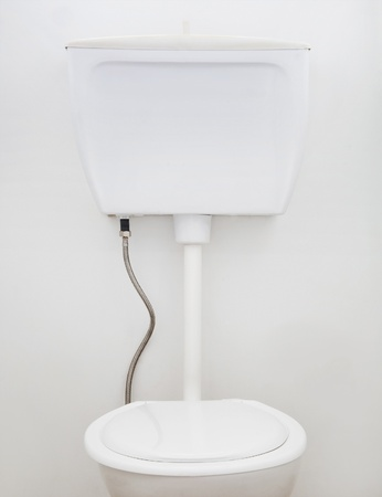 Generic white household toilet on white wall photo