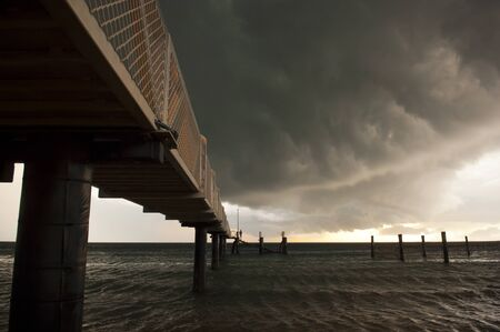 Huge black storm clouds gather as silhouetted people fish off a pier photo