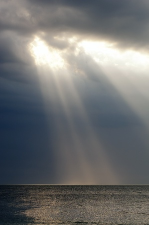 storm clouds: Amazing ray of light shines through storm clouds over ocean Stock Photo