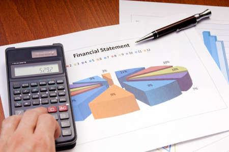 Graphs, calculator and paper statements for finance concept photo