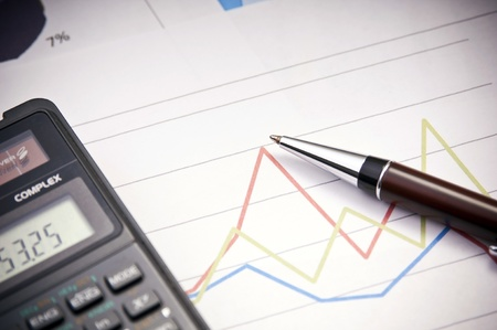 Graphs, calculator and paper statements for finance concept Stock Photo - 12596529