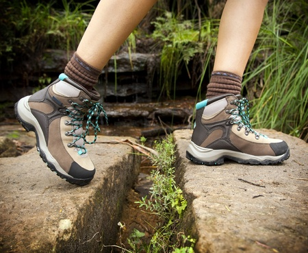 Fit young hiker crosses stone steps in hiking boots photo