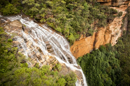australia landscape: Waterfall flows into valley below with thick forest Stock Photo