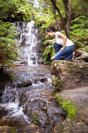 mountain pass: Young woman sits beside waterfall in the Blue Mountains, Australia