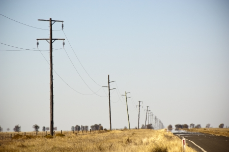 Heat haze rises as powerlines blur into the distance Stock Photo