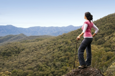 Single female hiker looks out at view in mountains with forest below her photo