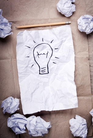 Crumpled paper with a lightbulb idea concept and crumpled paper attempts around it Stock Photo