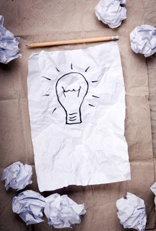 El papel arrugado con un concepto de idea de la bombilla y los intentos de papel arrugado que lo rodean