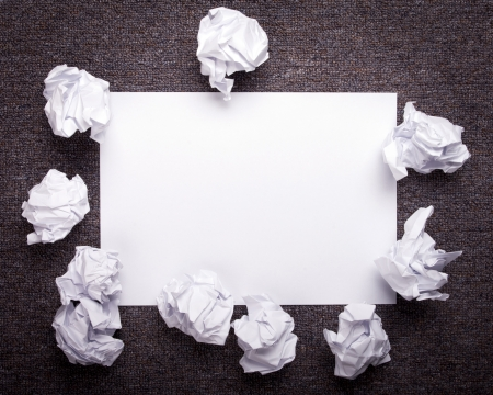 Crumpled and wrinkled white paper wads with fresh sheet of blank paper over dark texture