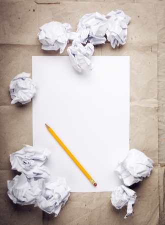 Writing concept - crumpled up paper wads with a sheet of white paper and pencil photo