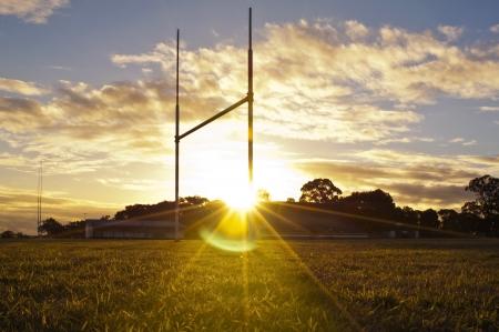pelota rugby: Postes de la porter�a de f�tbol, ??rugby o de la liga en el campo al atardecer Foto de archivo