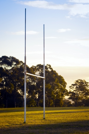 goal post: Goal posts for football, rugby union or league on field at sunset Stock Photo