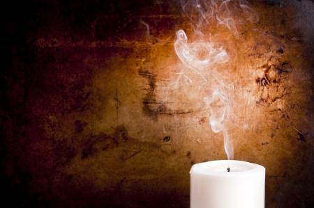 luz de velas: Rastros de humo en líneas suaves de una vela apagada con un fondo de la vendimia