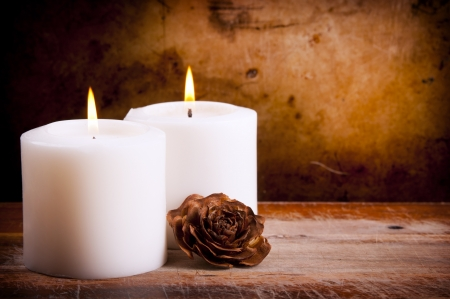 flickering: White candles burning with a textured vintage background