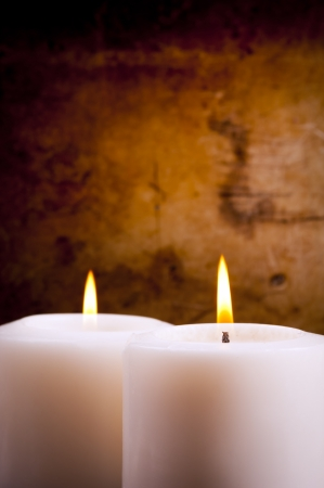lit candle: White candles burning with a textured vintage background