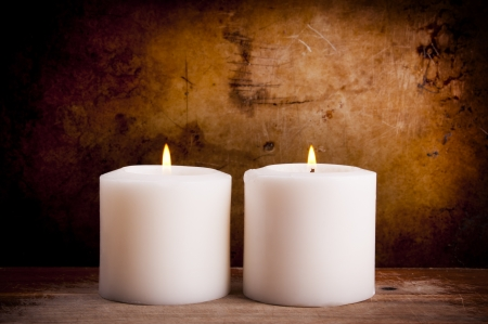 vigil: White candles burning with a textured vintage background