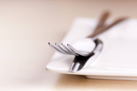 Knife and fork cutlery with a white place in very shallow focus Stock Photo - 14954050