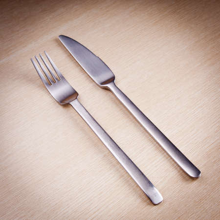 Knife and fork cutlery on a wooden table photo
