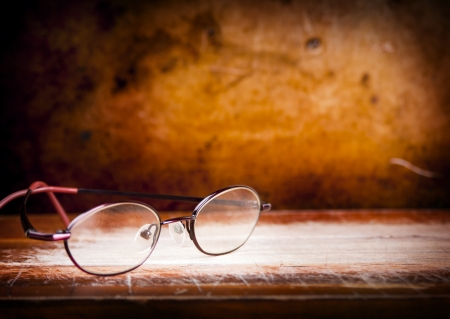 old writing: Pair of old eyglasses on a wooden desk with a grunge background