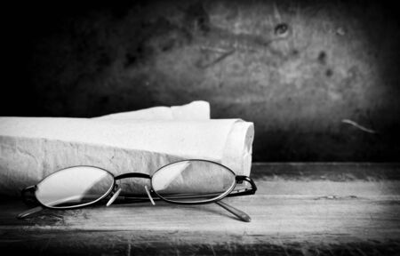 Pair of old eyglasses on a wooden desk with a grunge background photo