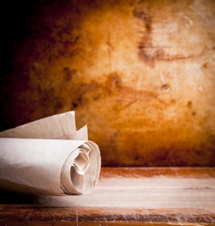 ancient books: Old paper parchment scroll rolled up with a vintage background with copy space Stock Photo