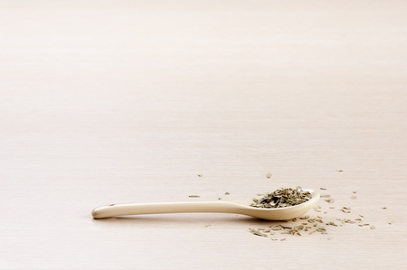 Tarragon in a spoon with some spilt over the wooden background photo