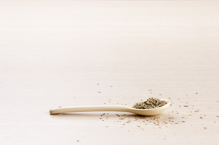 dried herbs: Thyme in a spoon with some spilt over the wooden background