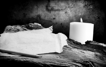 Vintage design of torn note paper with candle light and grunge background photo