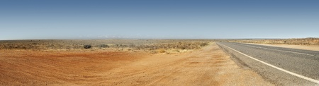 Panorama of the Australian Outback with red dirt and remote road photo