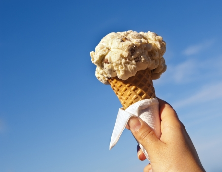 Icecream cone held up to the hot summer sky