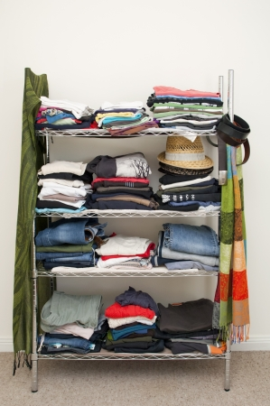 Clothes rack with stacked clothes for male and female, with jeans, T-shirts, scarves, hats and more photo