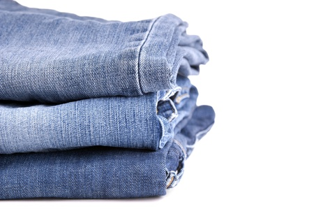 Blue jeans folded and stacked together, isolated on white photo