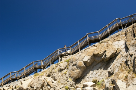 Young woman climbs up steep stairs on a mountain with blue sky behind as copy space photo